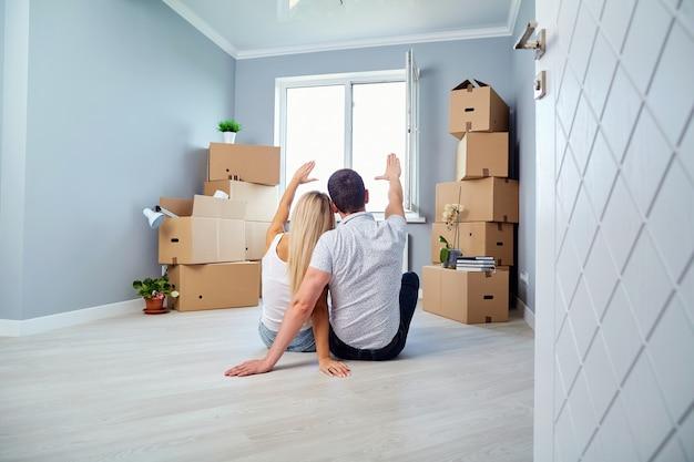Jovem casal no chão em uma casa nova