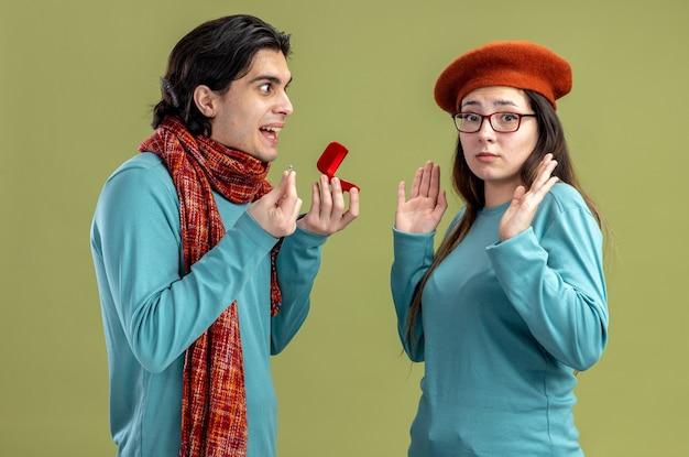 Jovem casal no dia dos namorados cara usando lenço garota usando chapéu cara sorridente dando aliança para garota isolada em fundo verde oliva