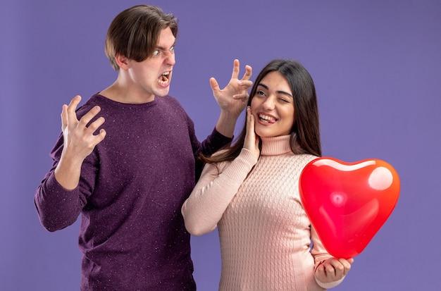 Jovem casal no dia dos namorados cara zangado olhando para a garota alegre segurando um balão, mostrando a língua colocando a mão na bochecha isolada sobre fundo azul