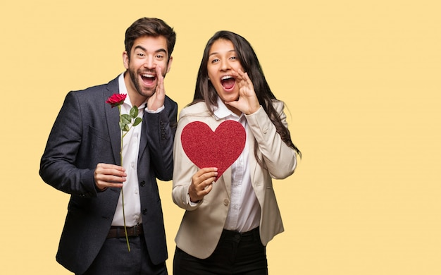 Jovem casal no dia dos namorados gritando algo feliz para a frente