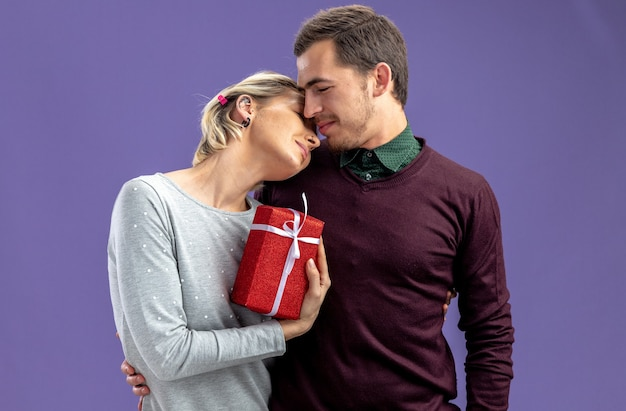 Jovem casal no dia dos namorados se abraçando, garota segurando uma caixa de presente isolada sobre fundo azul