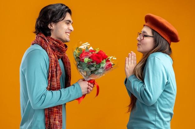 Jovem casal no dia dos namorados sorrindo cara usando lenço dando buquê para garota isolada em fundo laranja