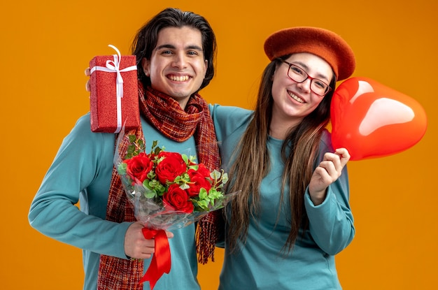 Jovem casal no dia dos namorados, sorrindo, garota segurando um balão de coração, abraçou cara com buquê isolado em fundo laranja