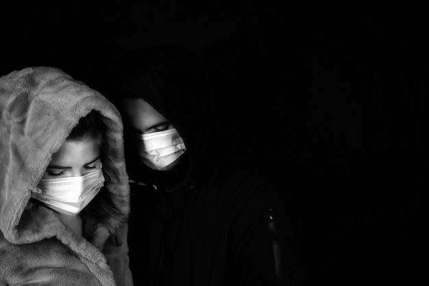Jovem casal no escuro com uma jaqueta de inverno e máscaras médicas protetoras