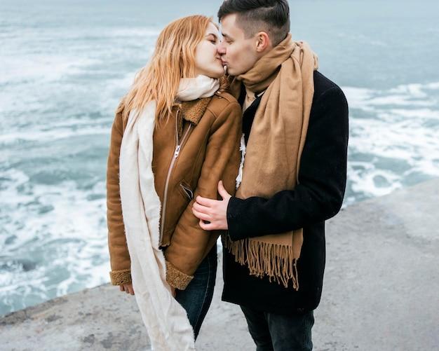 Jovem casal no inverno se beijando na praia