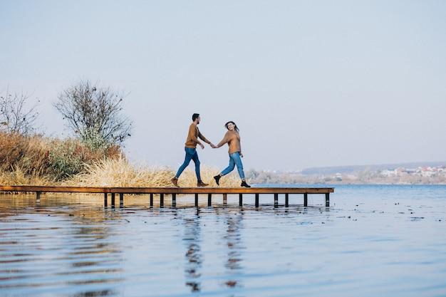 Jovem casal no parque em pé junto ao rio em pé na ponte do convés
