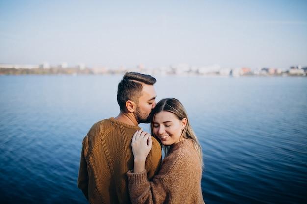 Jovem casal no parque em pé junto ao rio