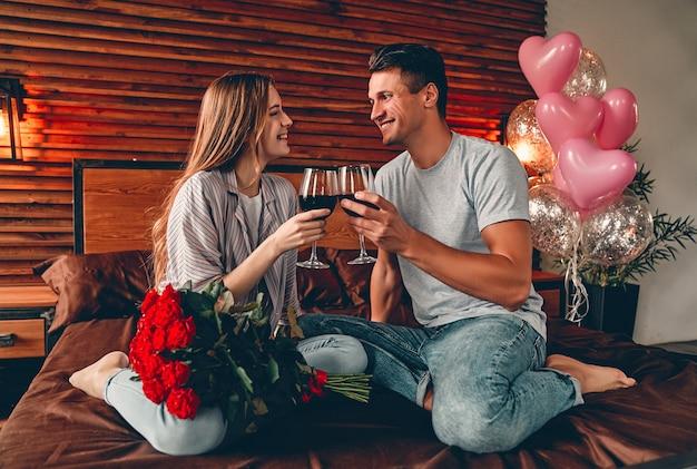 Jovem casal no quarto com taças de vinho e rosas vermelhas