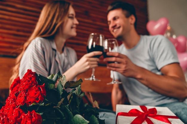 Jovem casal no quarto com taças de vinho, presente e rosas vermelhas