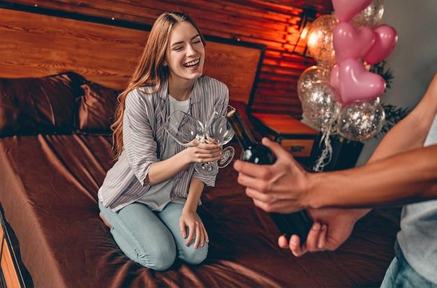 Jovem casal no quarto com taças e vinho