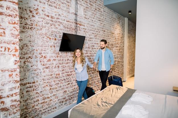 Jovem casal no quarto de hotel. começa as férias. jovem casal entrando em seu apartamento de férias ou quarto de hotel loft moderno com parede de tijolos