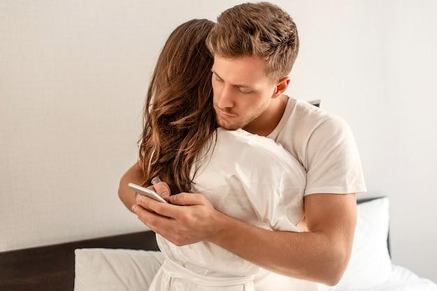 Jovem casal no quarto. um homem atraente está verificando as mensagens recebidas pela manhã