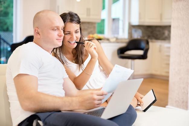 Jovem casal no sofá com o laptop e conta a conta para pagamento. o conceito de serviços públicos, dívida, pessoas e crédito.
