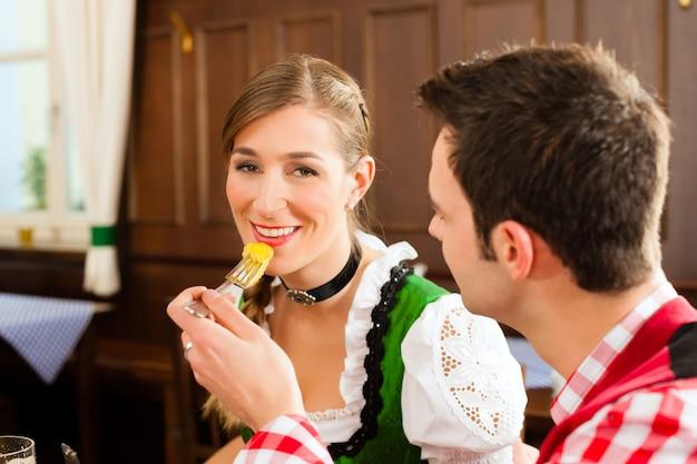 Jovem casal no tradicional tracht da baviera, comer no restaurante ou pub