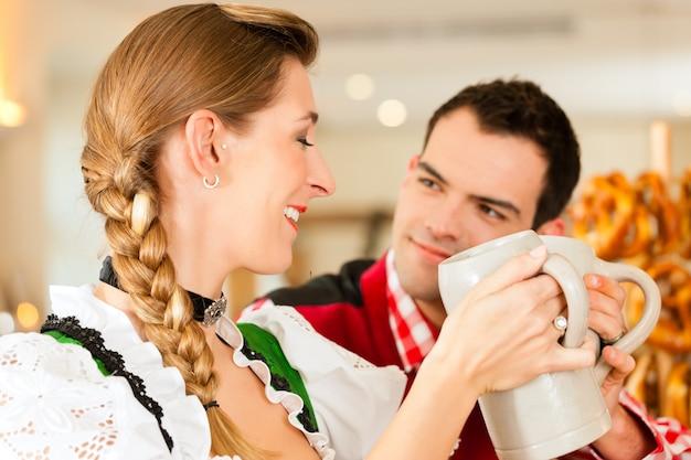 Jovem casal no tradicional tracht da baviera no restaurante ou pub
