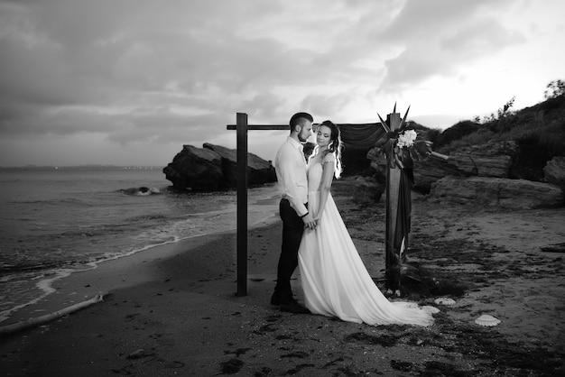 Jovem casal noivo e noiva com um buquê à noite na praia perto do arco de casamento