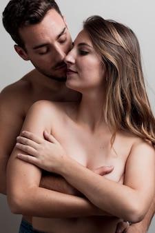 Jovem casal nu abraçando
