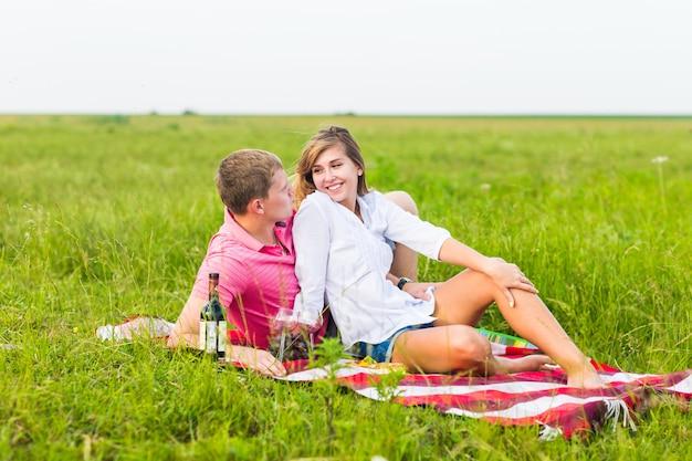 Jovem casal num prado de verão, homem e mulher fazendo um piquenique romântico.