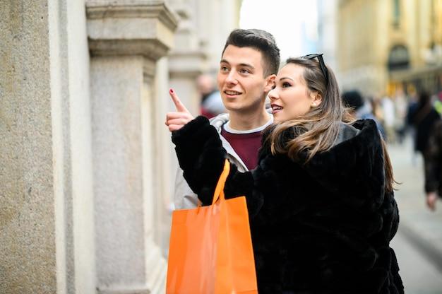 Jovem casal olhando animado em uma loja vitrine shile