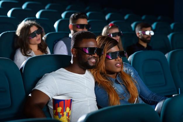 Jovem casal olhando interessado enquanto desfruta de um novo filme no cinema local Foto Premium