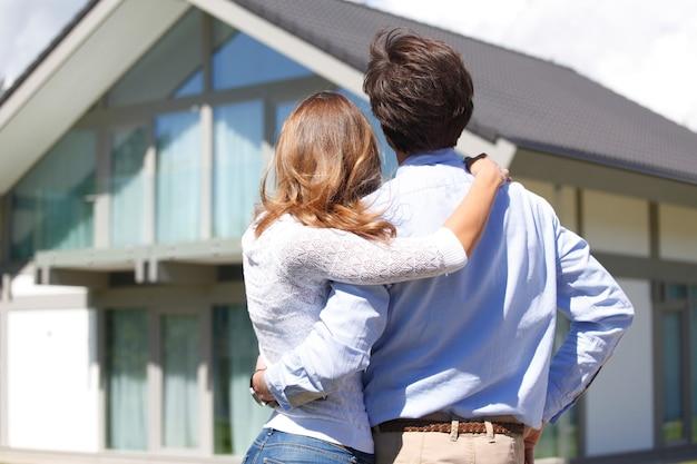 Jovem casal olhando para a casa