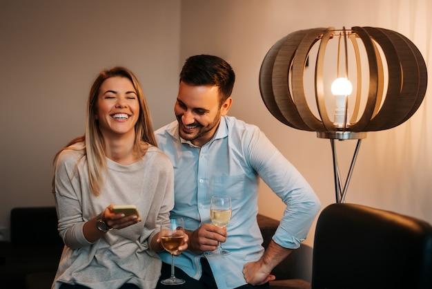 Jovem casal olhando para celular e rindo.