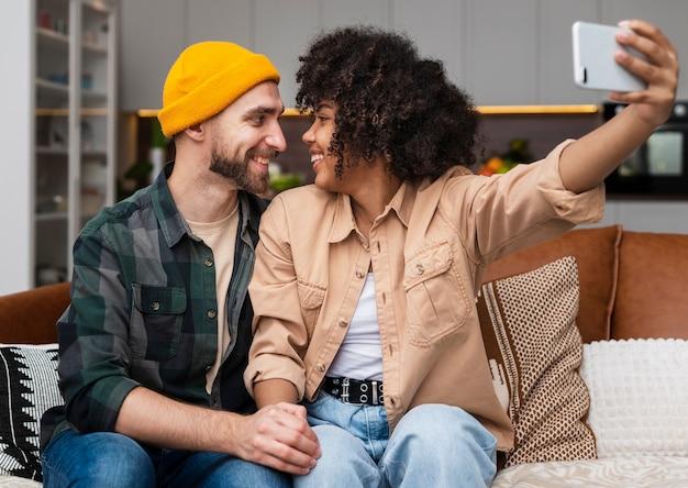 Jovem casal olhando um ao outro e tirar uma selfie