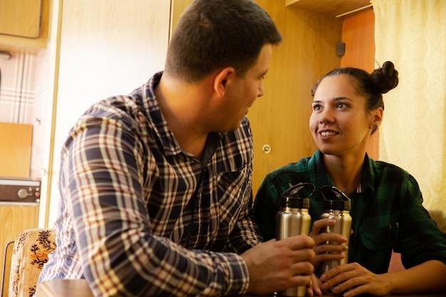 Jovem casal olhando um para o outro e segurando uma garrafa térmica dentro de um trailer. campista retrô