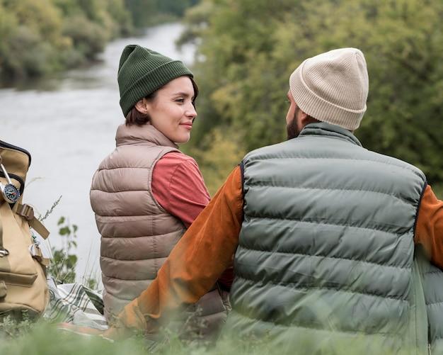 Jovem casal olhando um para o outro perto do rio