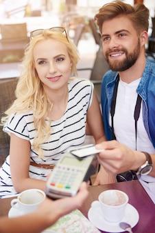 Jovem casal pagando pelo café
