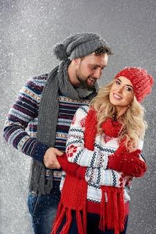 Jovem casal parado na nevasca