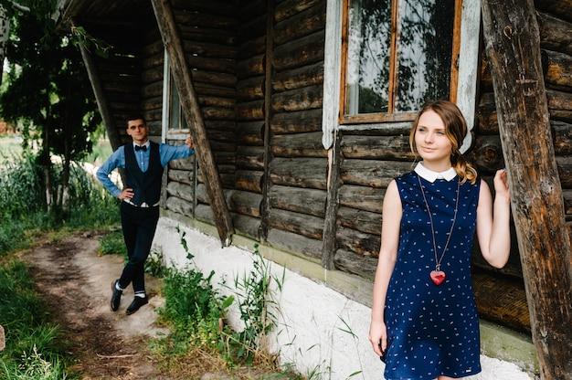 Jovem casal parado perto de uma velha casa de madeira elegante na superfície da bétula e da natureza