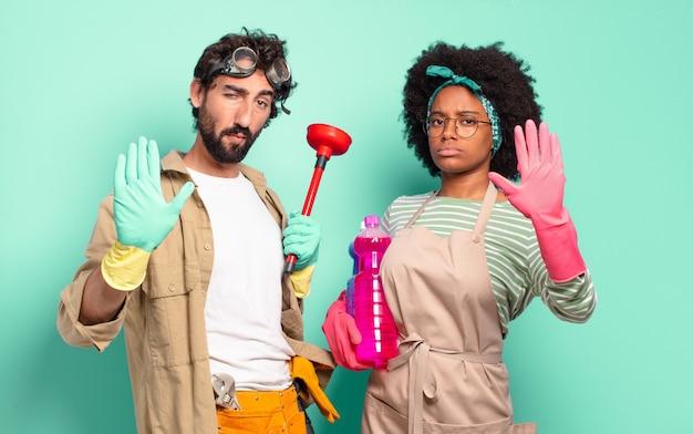 Jovem casal parecendo sério, severo, descontente e irritado, mostrando a palma da mão aberta fazendo gesto de pare