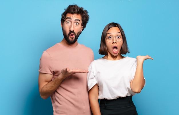 Jovem casal parecendo surpreso e chocado, com o queixo caído segurando um objeto com a mão aberta na lateral