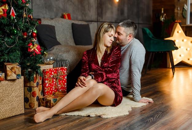 Jovem casal passando o natal juntos. lindo casal se abraçando perto da árvore de natal. casal apaixonado sentado ao lado de uma árvore de natal curtindo momentos românticos
