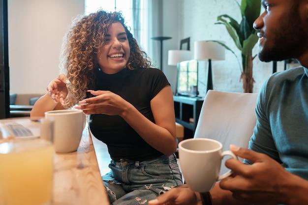 Jovem casal passando um bom tempo juntos enquanto bebe uma xícara de café em casa.