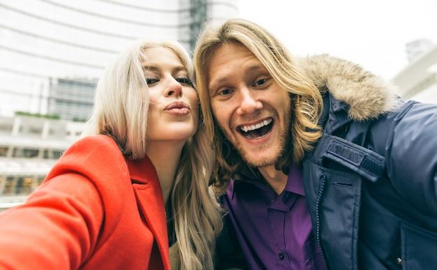 Jovem casal passar o tempo da tarde no centro da cidade de milão e tirar selfies