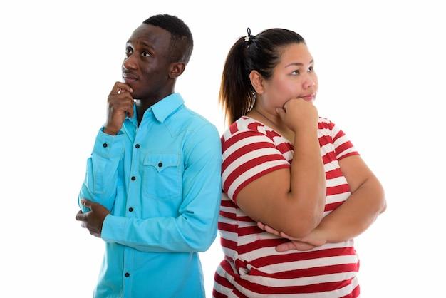 Jovem casal pensando e planejando enquanto olha para cima