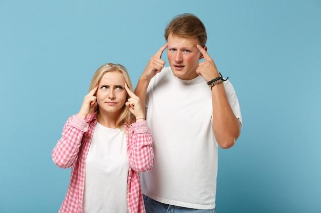 Jovem casal pensativo, dois amigos, homem e mulher, em camisetas brancas rosa vazias em branco posando