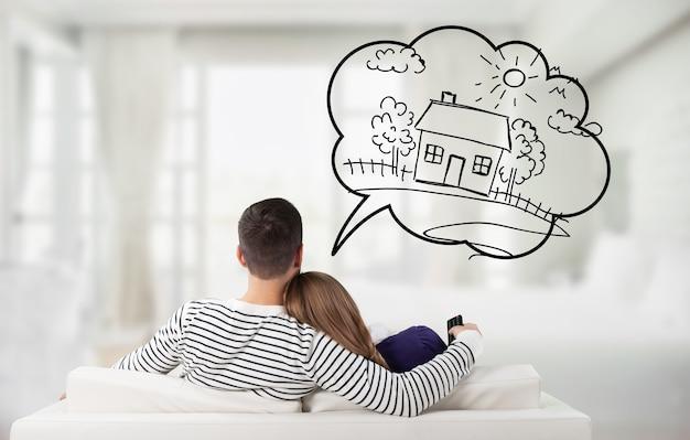 Jovem casal pensativo sentado no sofá pensando em comprar sua própria casa