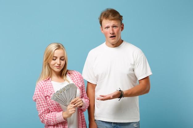 Jovem casal perplexo, dois amigos, cara e mulher em camisetas brancas rosa posando