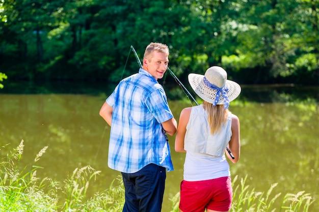 Jovem casal pescando ou pescando em pé na margem do rio na grama