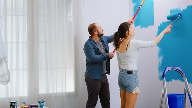 Jovem casal pintando a parede com escova de rolo durante a renovação da casa. redecoração de apartamento e construção de casa durante a reforma e melhoria. reparação e decoração.
