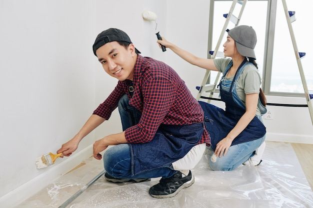 Jovem casal pintando parede