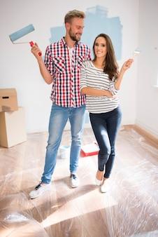 Jovem casal pintando uma parede azul