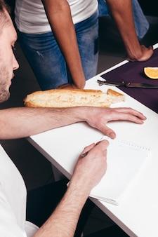 Jovem casal planeja o futuro e escreve uma lista de tarefas no caderno