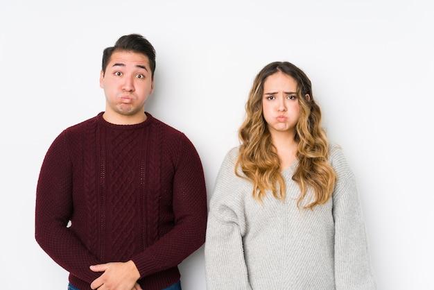 Jovem casal posando em um fundo branco, soprando nas bochechas, com expressão de cansaço