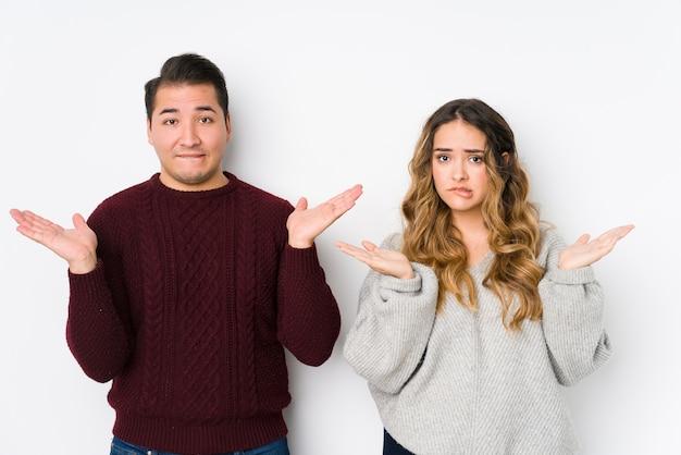 Jovem casal posando em uma parede branca confuso e duvidoso, encolhendo os ombros para segurar um espaço de cópia.