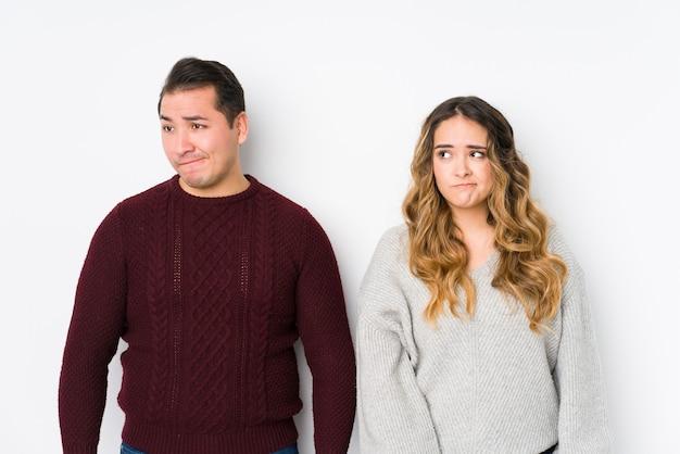 Jovem casal posando em uma parede branca confuso, sente-se em dúvida e inseguro.