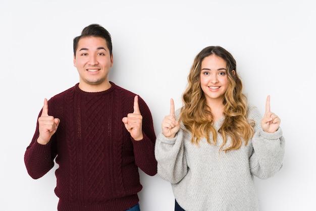 Jovem casal posando em uma parede branca indica com os dois dedos dianteiros, mostrando um espaço em branco.